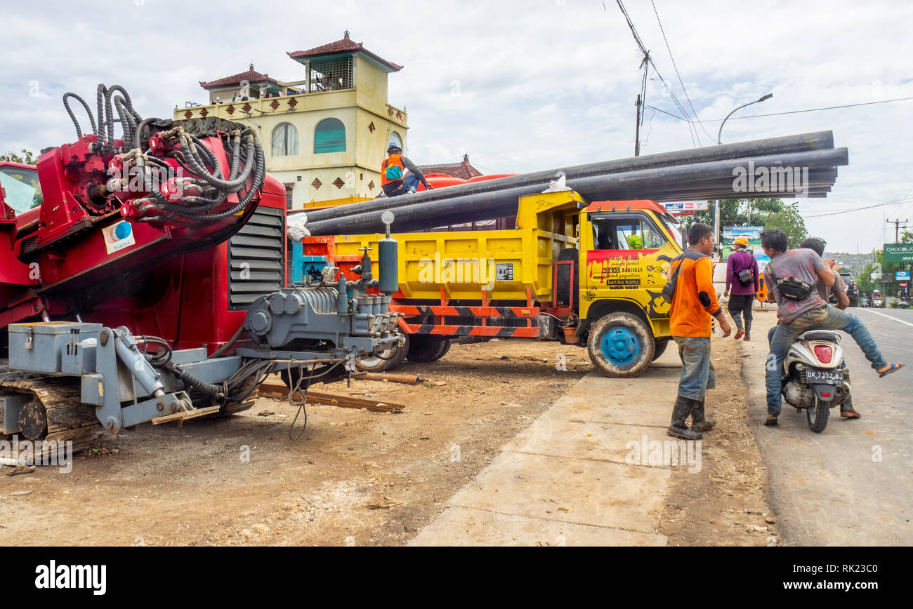 Workmen in a yard unloading pipes from a truck, and heavy equipment,  in Jimbaran, Bali Indonesia., Bali Indonesia. - Stock Image