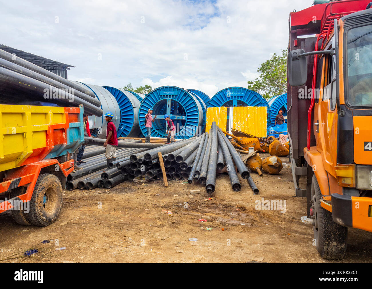Workmen in a yard unloading pipes from a truck in Jimbaran, Bali Indonesia. - Stock Image