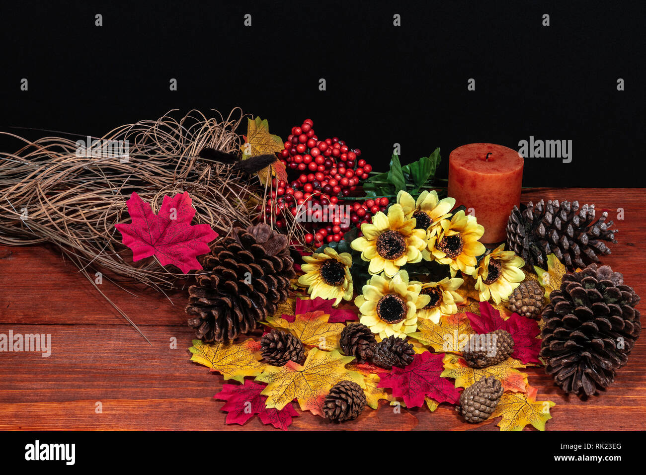 Silk maple leaves, beautiful bouquet of sunflowers, frosted pinecones and orange candle on tabletop with dark background. Stock Photo
