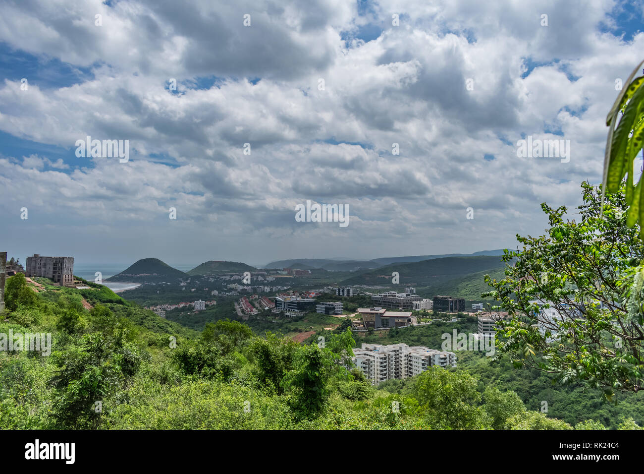 Awesome view of city building from top of a mountain with white sky cloud. Stock Photo