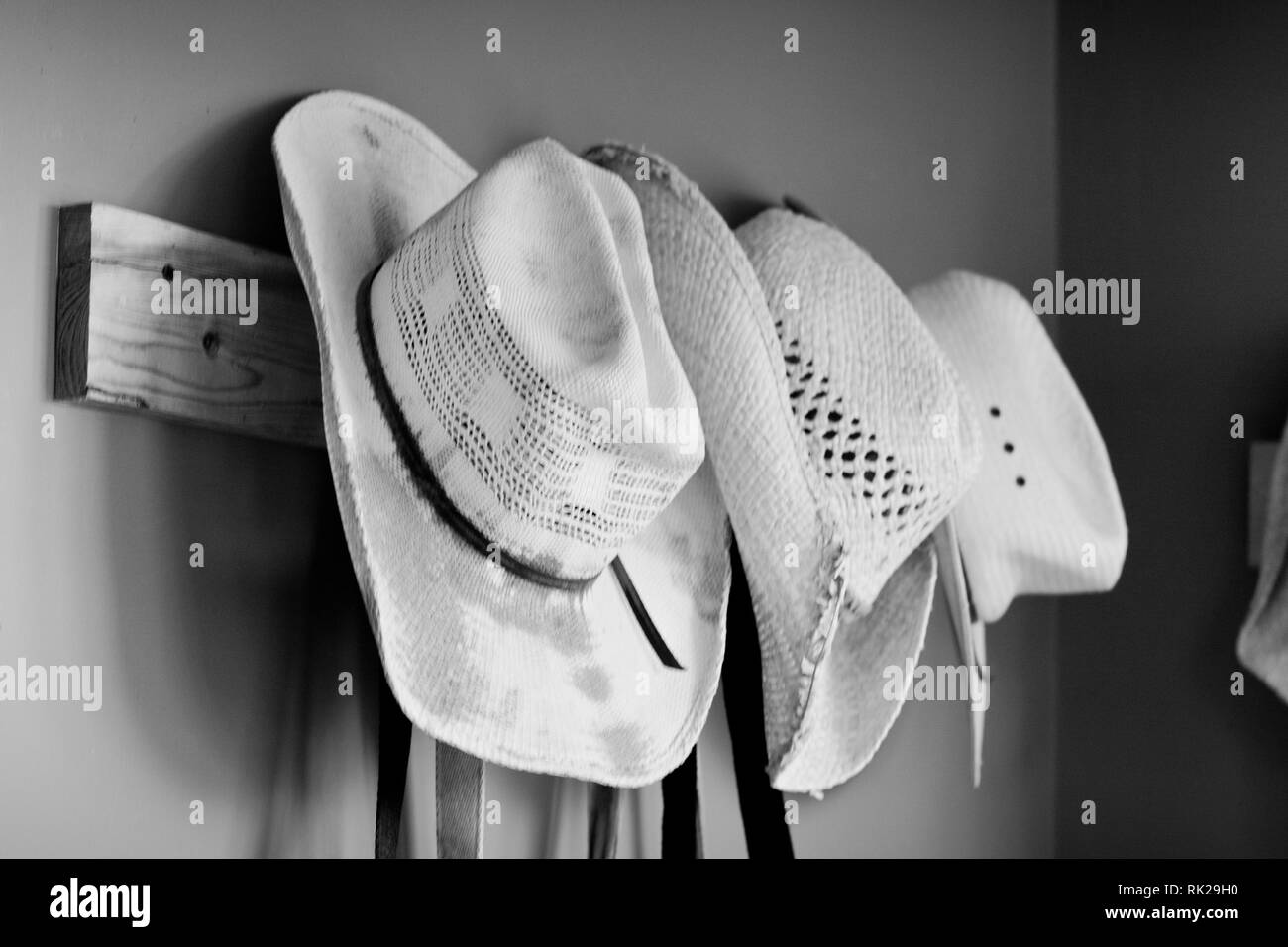 straw hats hanging on wall - Stock Image
