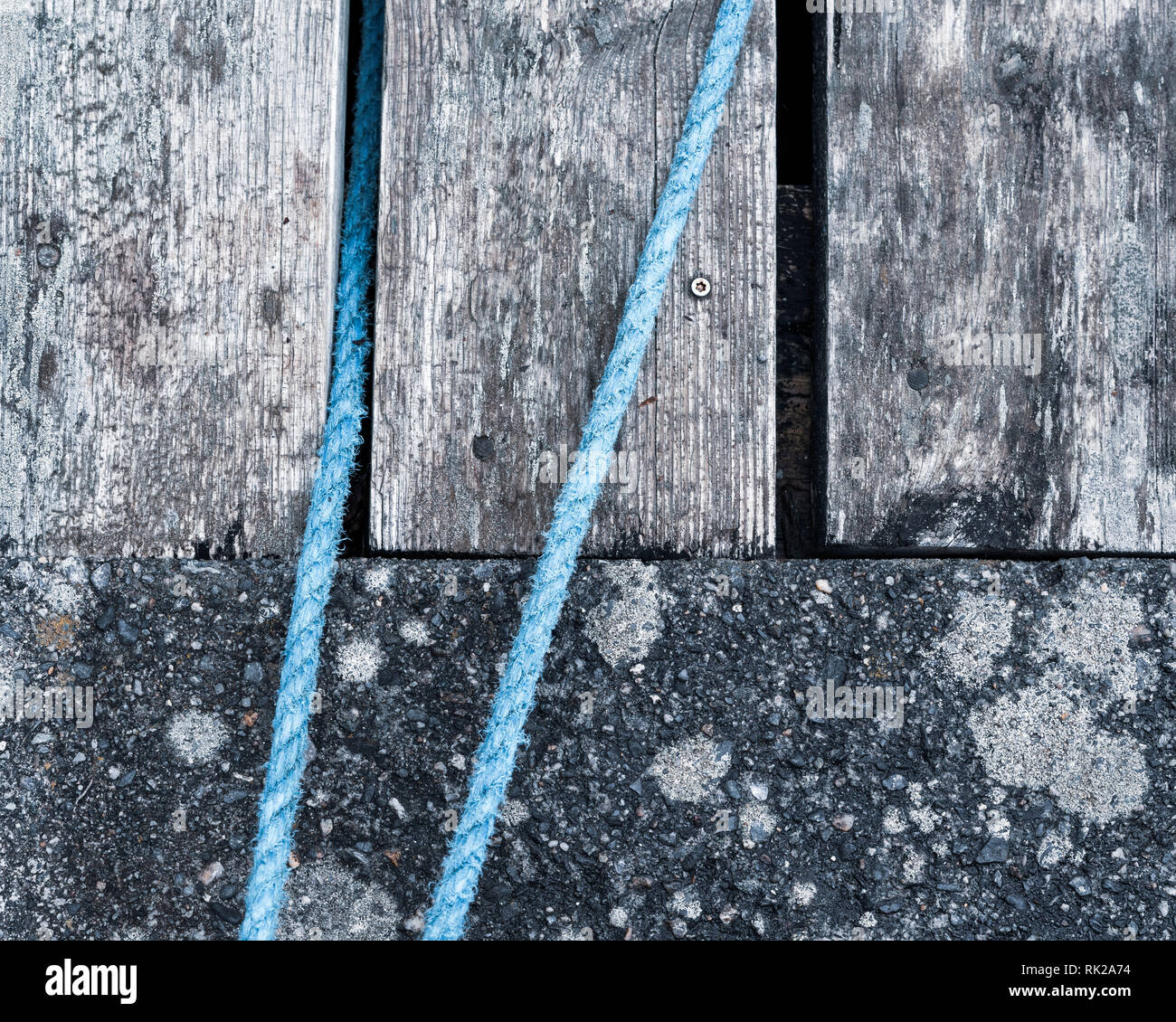 Weathered wooden planks and concrete with blue rope, full frame, close up - Stock Image