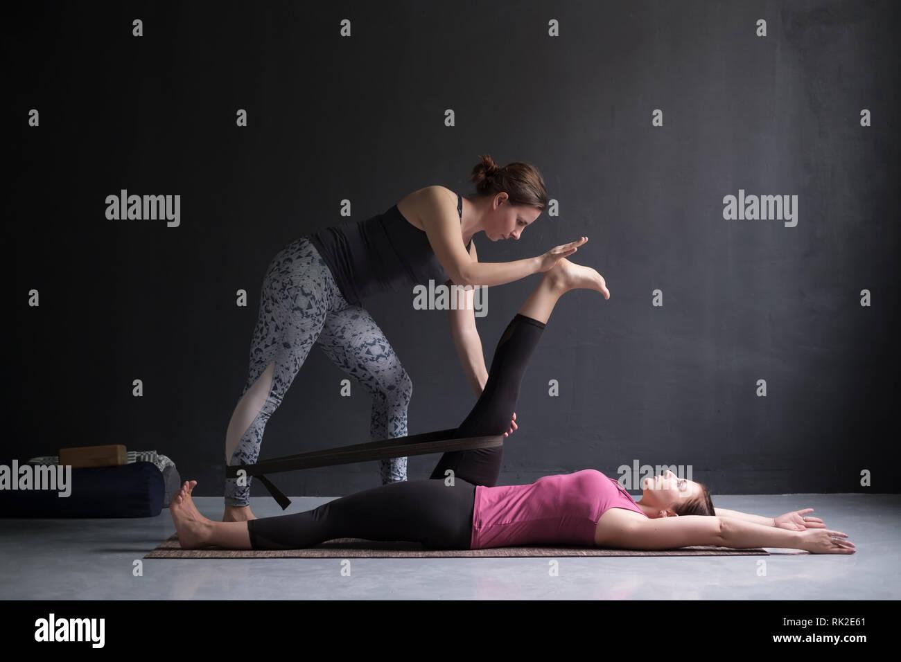 Coach helping girl to do reclining hand to big toe pose, supta padangusthasana - Stock Image