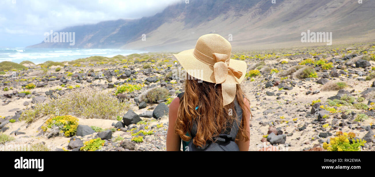 Rear view of traveler girl with straw hat looking at beautiful natural landscape. Young female backpacker exploring Lanzarote, Canary Islands. Banner  Stock Photo