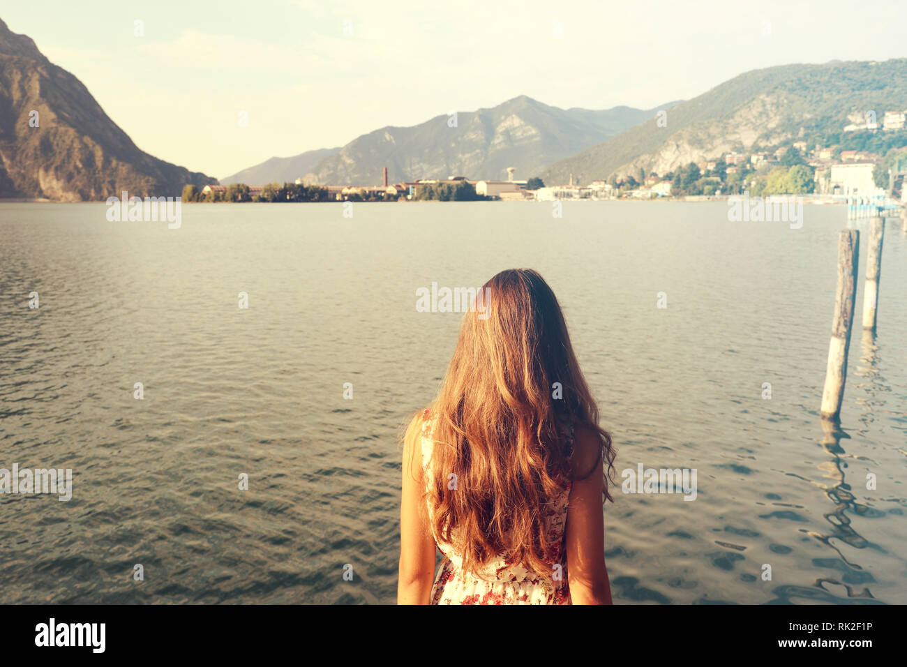 Attractive girl standing backwards and watching nature. Woman back view on lake. Vintage filter. - Stock Image