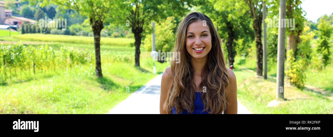 Active cheerful woman pausing after a run in a park on a sunny day. Fit smiling girl looking at camera in a park on spring or summer. - Stock Image