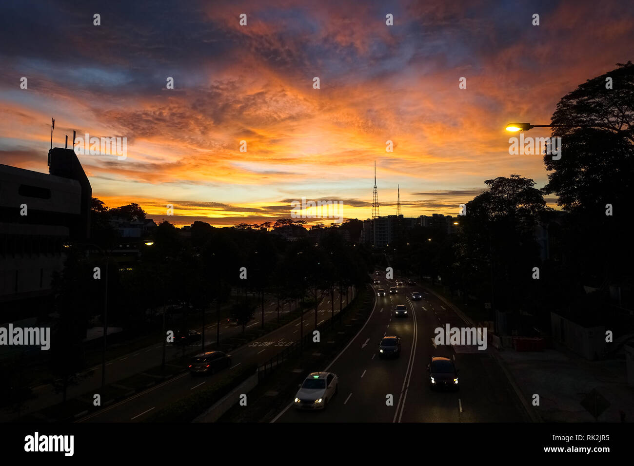 Traffic Headlights and Pink Sunset in Clouds Over Bukit Timah Rd. - Singapore City - Stock Image