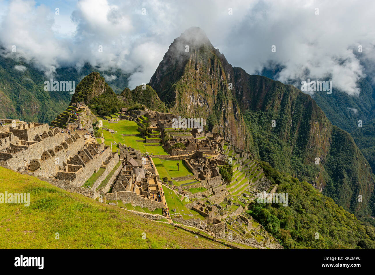 The lost Inca ruin city of Machu Picchu in the morning fog with its green terraced field and Huayna Picchu peak in the background near Cusco, Peru. - Stock Image