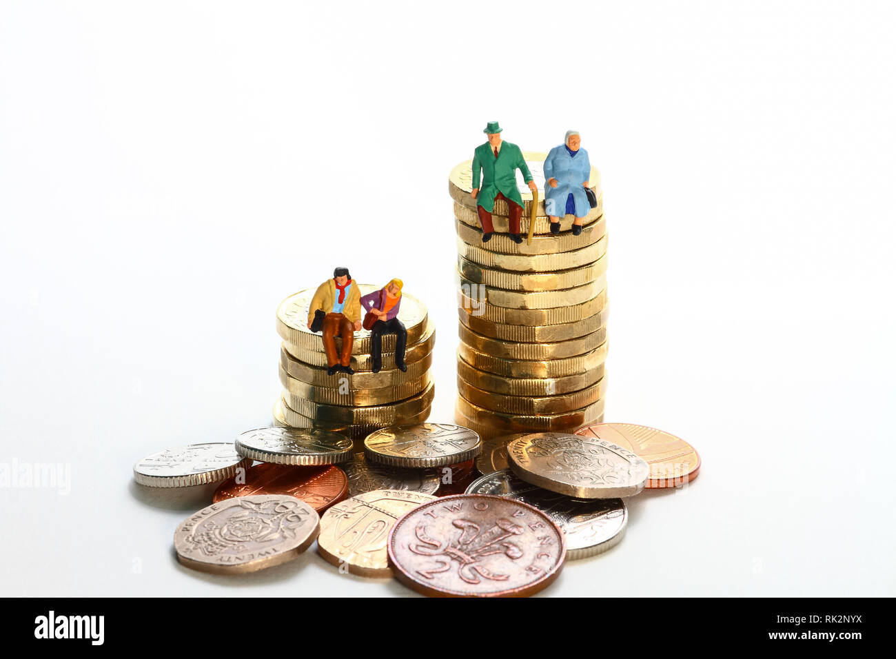 Conceptual diorama image of a miniture figure retired couple and young couple sat on a stack of pound coins - Stock Image