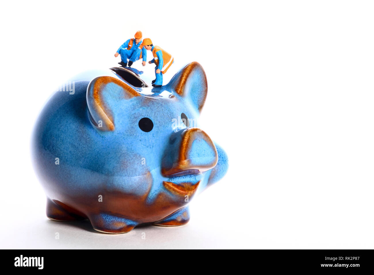 Conceptual diorama image of miniature figure workmen peering in to a piggy bank money box - Stock Image
