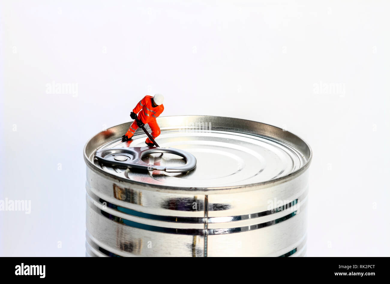 Conceptual diorama image of miniature figure workman trying to open a tin can, - Stock Image