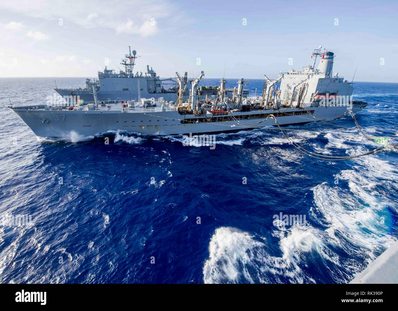 190207-N-PH222-1022 PACIFIC OCEAN (Feb. 7, 2019) Fleet replenishment oiler USNS Pecos (T-AO 197), center, conducts a vertical replenishment with the Whidbey Island-class amphibious dock landing ship USS Rushmore (LSD 47), top, and the San Antonio-class amphibious transport dock ship USS Anchorage (LPD 23) during a deployment of the Essex Amphibious Ready Group (ARG) and 13th Marine Expeditionary Unit (MEU). The Essex ARG/13th MEU is a capable and lethal Navy-Marine Corps team deployed to the 7th fleet area of operations to support regional stability, reassure partners and allies and maintain a - Stock Image