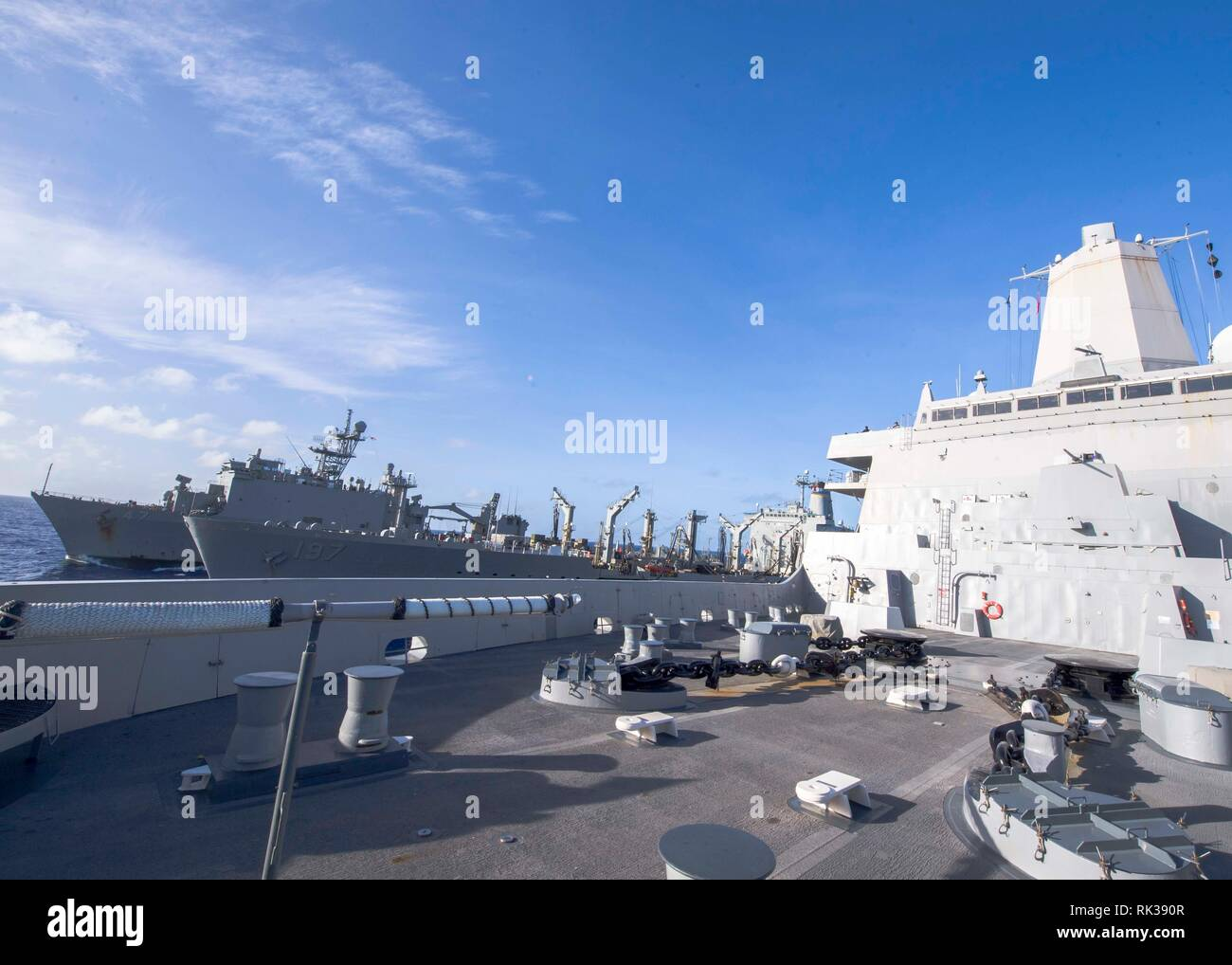 190207-N-PH222-1042 PACIFIC OCEAN (Feb. 7, 2019) The San Antonio-class amphibious transport dock ship USS Anchorage (LPD 23), right, participates in an underway replenishment with fleet replenishment oiler USNS Pecos (T-AO 197), center, and the Whidbey Island-class amphibious dock landing ship USS Rushmore (LSD 47) during a deployment of the Essex Amphibious Ready Group (ARG) and 13th Marine Expeditionary Unit (MEU). The Essex ARG/13th MEU is a capable and lethal Navy-Marine Corps team deployed to the 7th fleet area of operations to support regional stability, reassure partners and allies and  - Stock Image