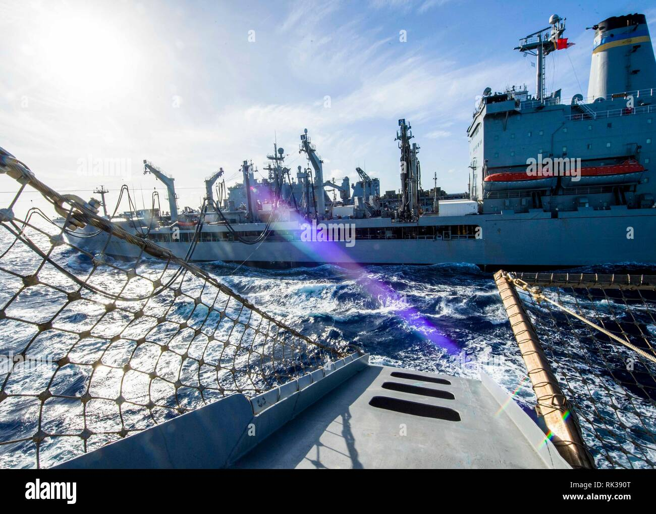 190207-N-PH222-1165 PACIFIC OCEAN (Feb. 7, 2019) The San Antonio-class amphibious transport dock ship USS Anchorage (LPD 23) participates in an underway replenishment with fleet replenishment oiler USNS Pecos (T-AO 197) while on a deployment of the Essex Amphibious Ready Group (ARG) and 13th Marine Expeditionary Unit (MEU). The Essex ARG/13th MEU is a capable and lethal Navy-Marine Corps team deployed to the 7th fleet area of operations to support regional stability, reassure partners and allies and maintain a presence postured to respond to any crisis ranging from humanitarian assistance to c - Stock Image