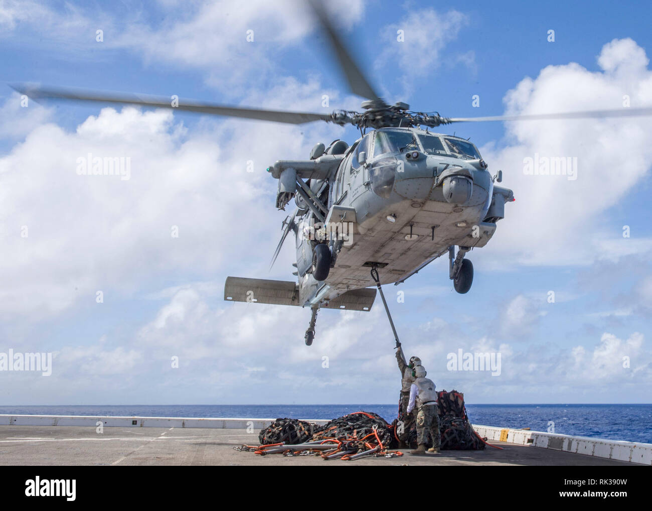 """190207-N-PH222-1433 PACIFIC OCEAN (Feb. 7, 2019) A MH-60S Sea Hawk helicopter, attached to the """"Blackjacks"""" of Helicopter Sea Combat Squadron (HSC) 21, prepares to transport cargo from the flight deck aboard the San Antonio-class amphibious transport dock ship USS Anchorage (LPD 23) during a vertical replenishment. Anchorage is on a deployment of the Essex Amphibious Ready Group (ARG) and 13th Marine Expeditionary Unit (MEU). The Essex ARG/13th MEU is a capable and lethal Navy-Marine Corps team deployed to the 7th fleet area of operations to support regional stability, reassure partners and al - Stock Image"""