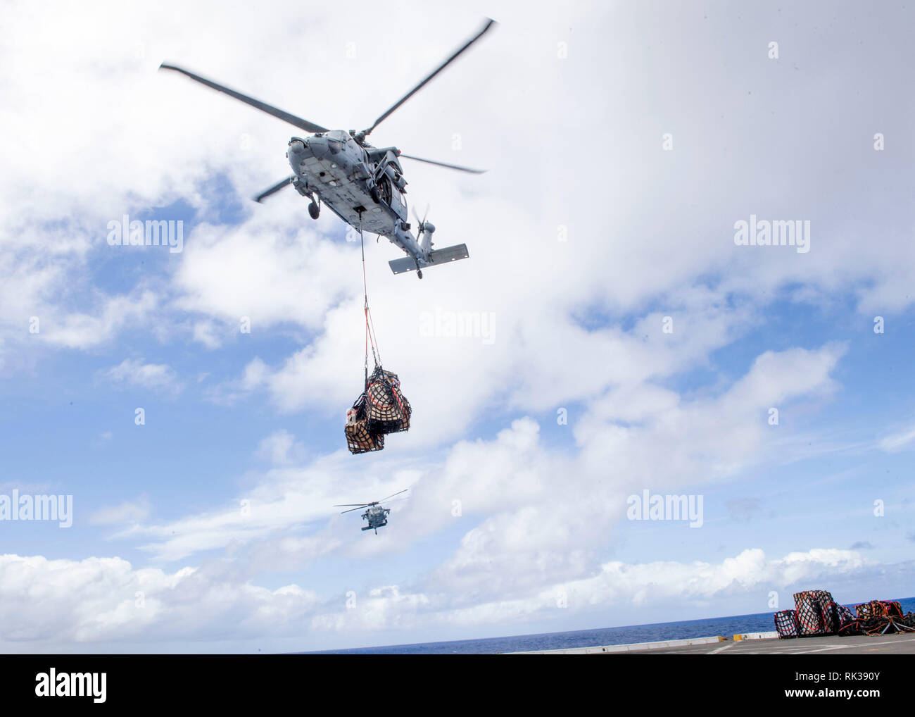 """190207-N-PH222-1319 PACIFIC OCEAN (Feb. 7, 2019) A MH-60S Sea Hawk helicopter, attached to the """"Blackjacks"""" of Helicopter Sea Combat Squadron (HSC) 21, delivers cargo to the flight deck of the San Antonio-class amphibious transport dock ship USS Anchorage (LPD 23) during a vertical replenishment. Anchorage is on a deployment of the Essex Amphibious Ready Group (ARG) and 13th Marine Expeditionary Unit (MEU). The Essex ARG/13th MEU is a capable and lethal Navy-Marine Corps team deployed to the 7th fleet area of operations to support regional stability, reassure partners and allies and maintain a - Stock Image"""
