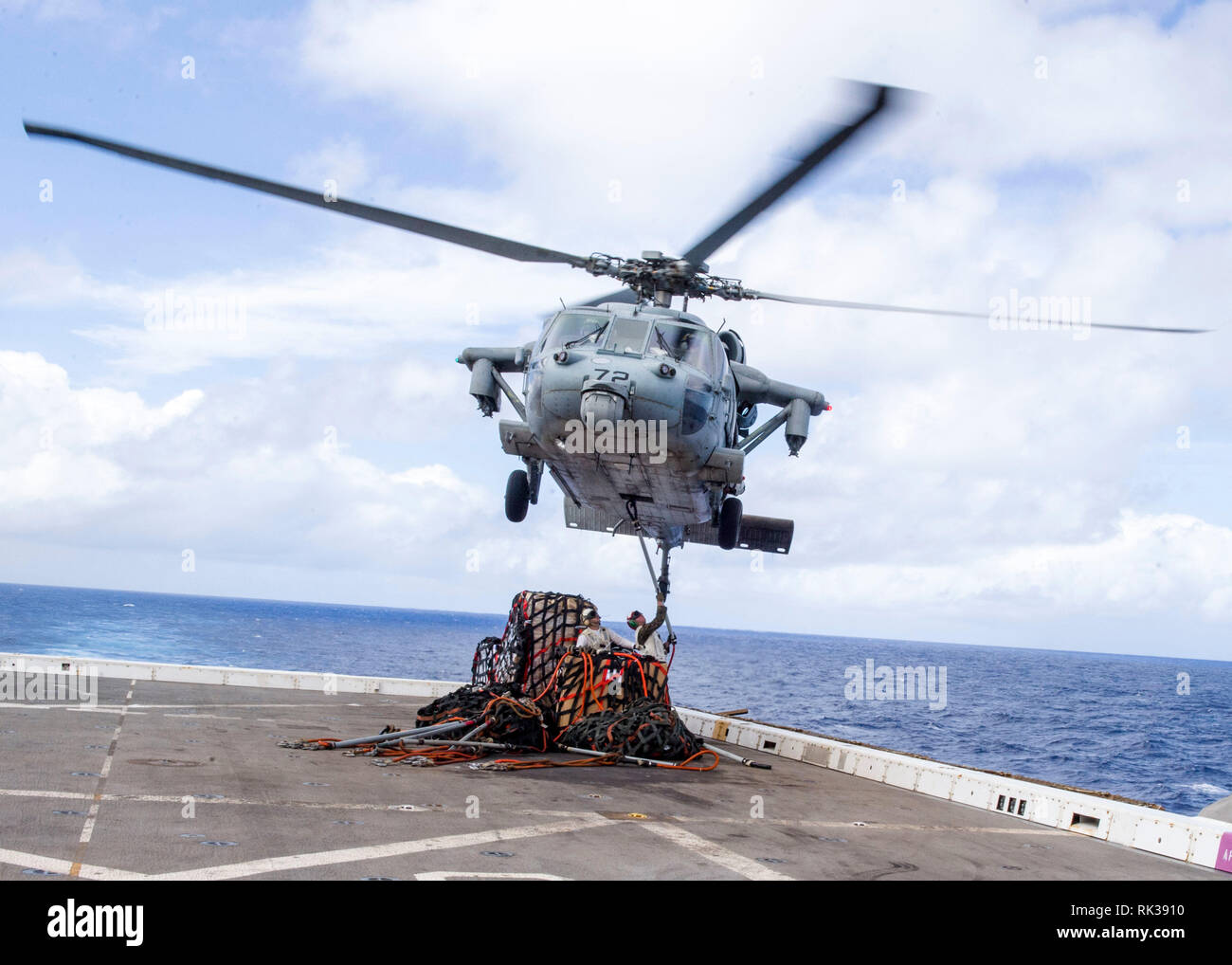 """190207-N-PH222-1335 PACIFIC OCEAN (Feb. 7, 2019) A MH-60S Sea Hawk helicopter, attached to the """"Blackjacks"""" of Helicopter Sea Combat Squadron (HSC) 21, prepares to transport cargo from the flight deck of the San Antonio-class amphibious transport dock ship USS Anchorage (LPD 23) during a vertical replenishment. Anchorage is on a deployment of the Essex Amphibious Ready Group (ARG) and 13th Marine Expeditionary Unit (MEU). The Essex ARG/13th MEU is a capable and lethal Navy-Marine Corps team deployed to the 7th fleet area of operations to support regional stability, reassure partners and allies - Stock Image"""