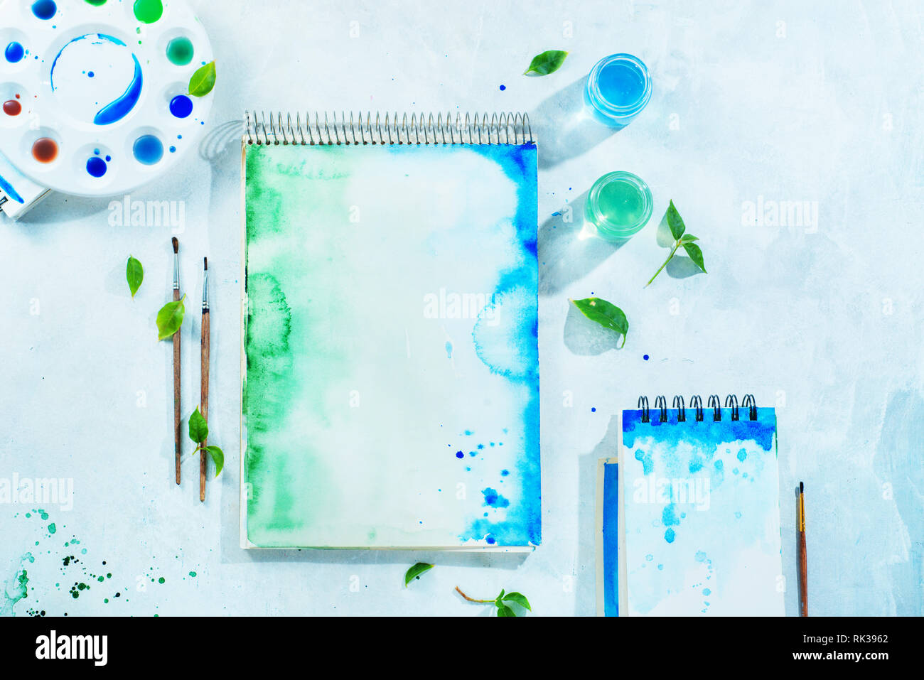 Painting spring concept with artist tools, green and blue watercolor sketchbooks, brushes and color palette on a white background with copy space - Stock Image