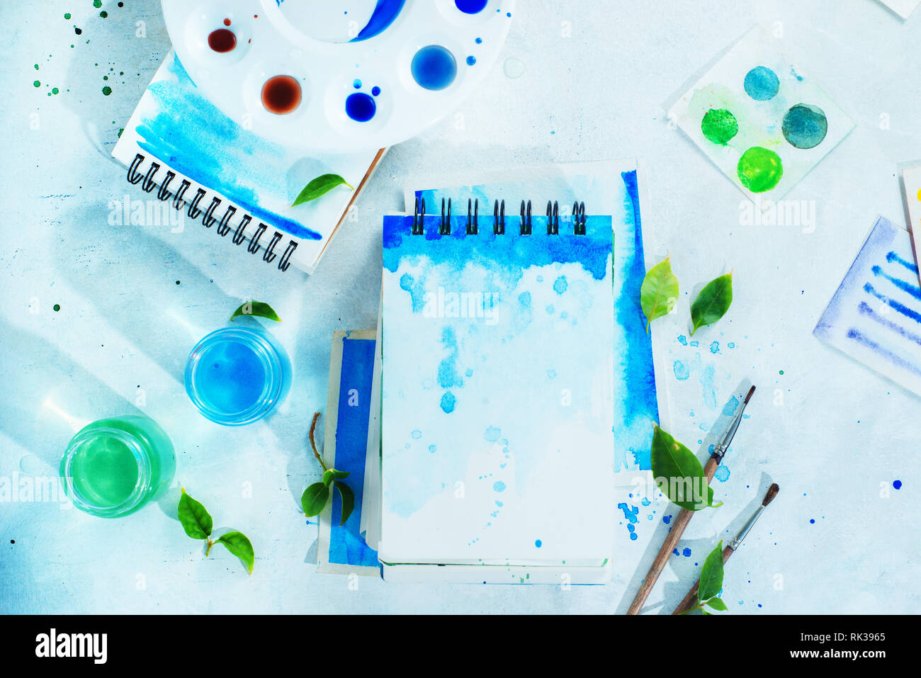 Drawing spring concept with artist tools, green and blue watercolor sketchbooks, brushes and color palette on a light background with copy space - Stock Image