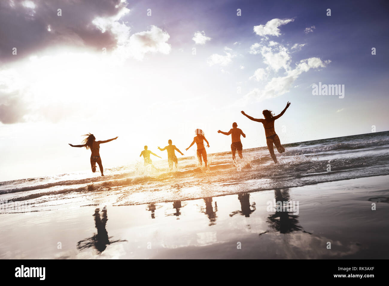 Group of happy peoples runs and jumps at sunset sea beach. Tropical tourism concept Stock Photo