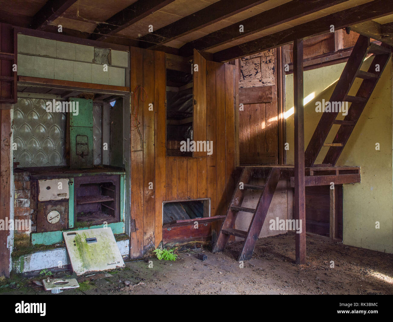 Broken wood stove and ladders to loft, interior of abandoned house, Ahu Ahu Ohu, Whanganui River, North Island, New Zealand - Stock Image