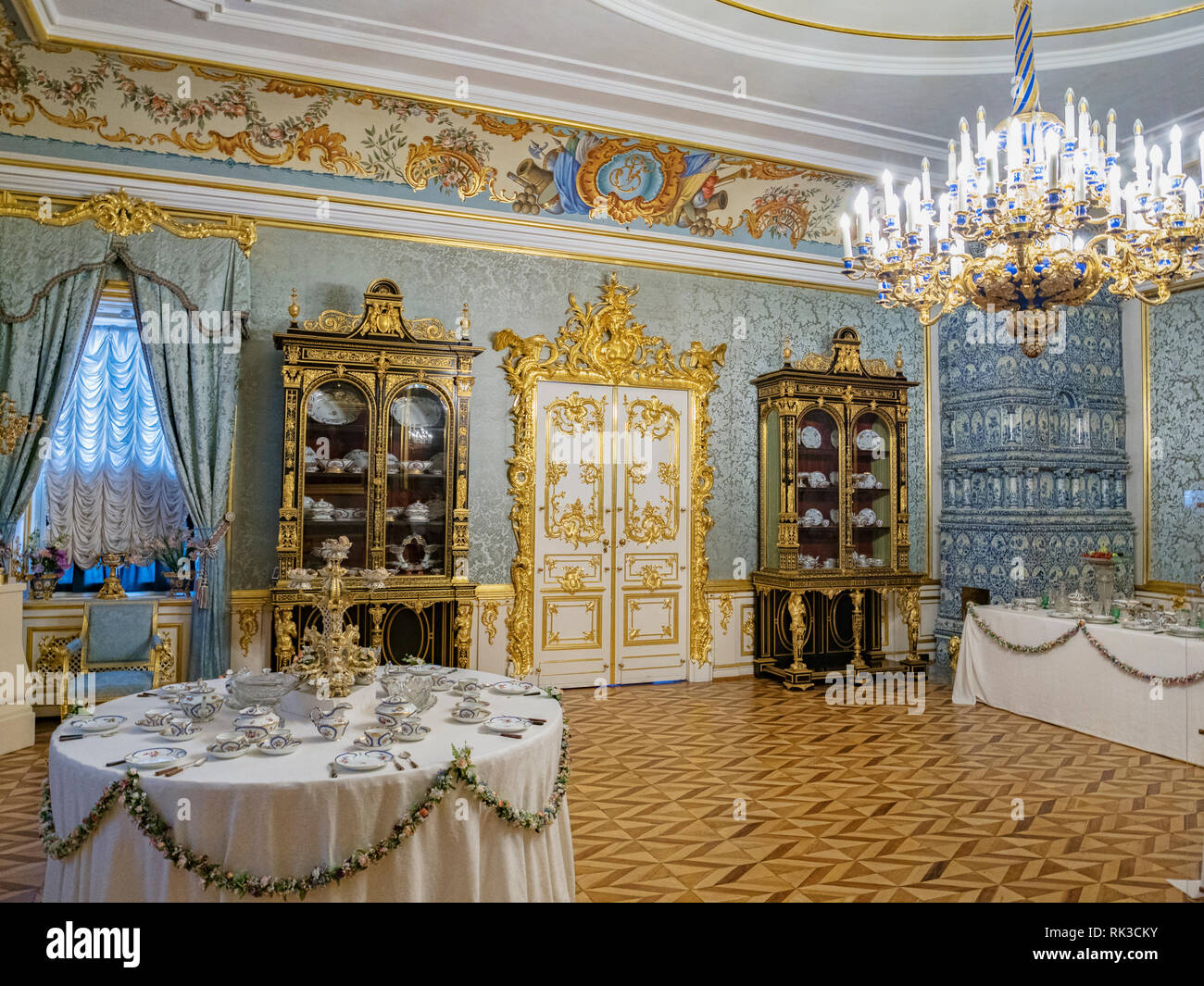 18 September 2018: St Petersburg, Russia - An ornate room in the Peterhof Palace, with chandelier and table set for tea. - Stock Photo