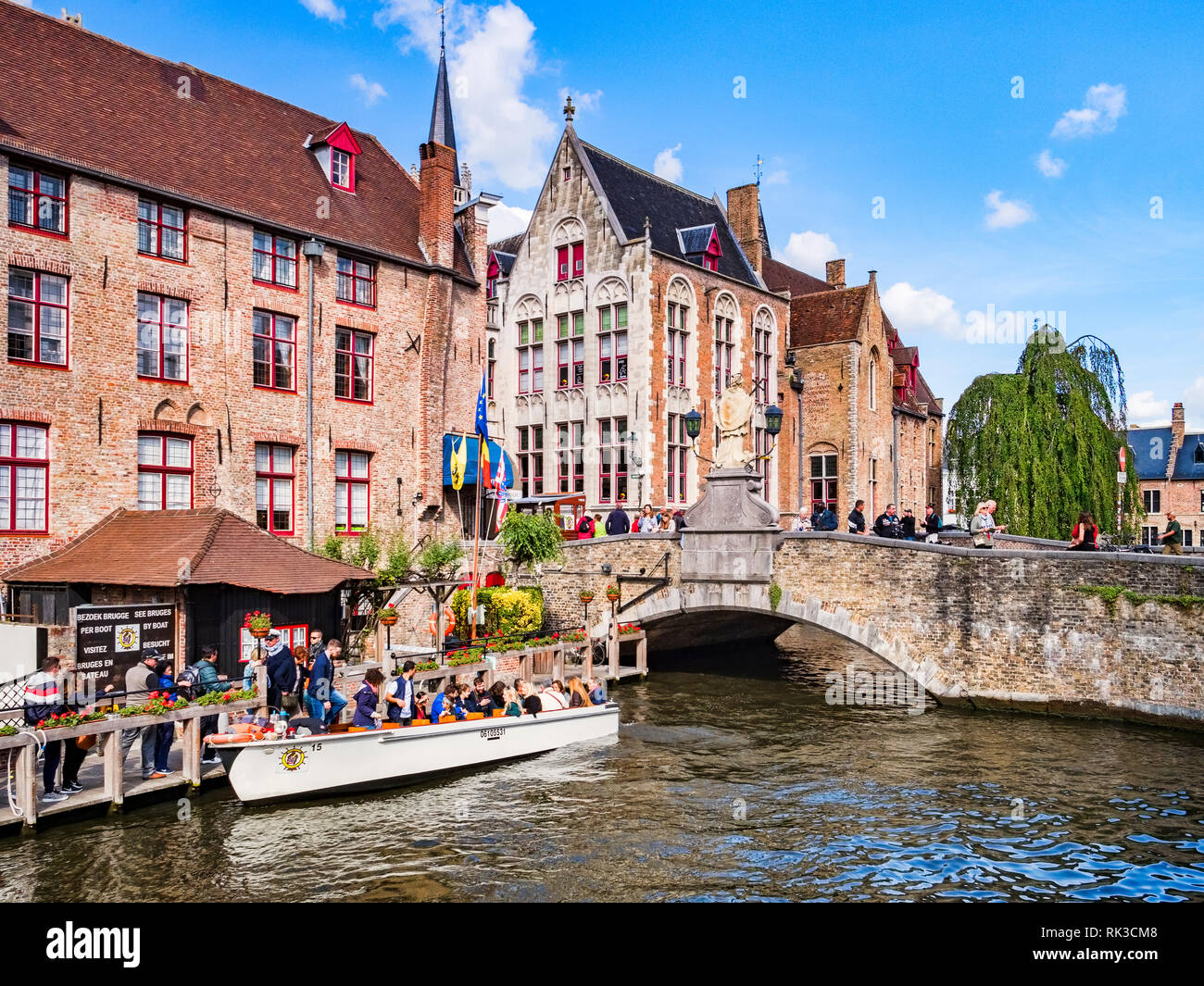 25 September 2018: Bruges, Belgium - Tourists boarding a tour boat on the canal by the Wollestraat Bridge in Bruges. Stock Photo
