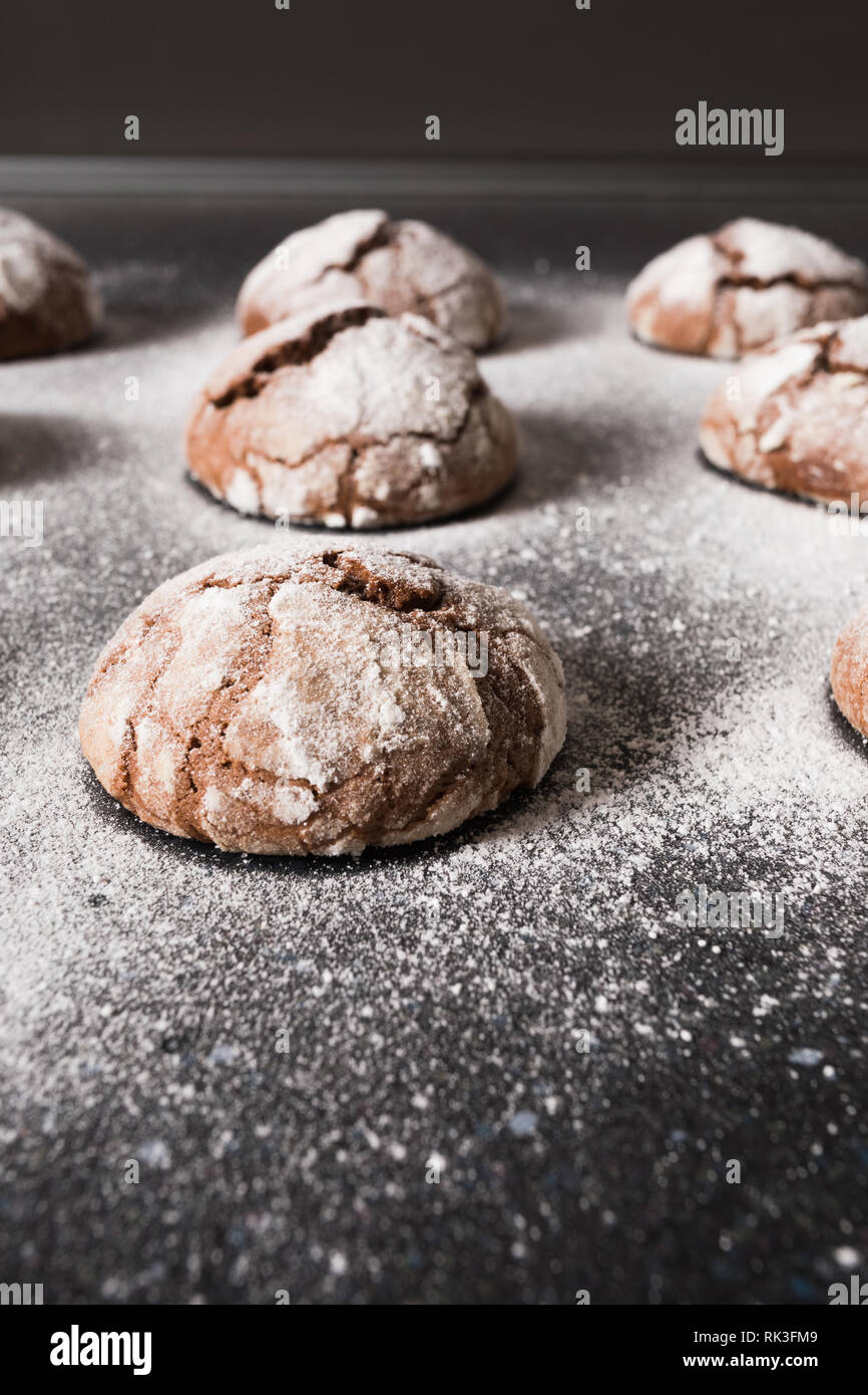 Delicious chocolate chip cookies with beautiful cracks and dusted with icing sugar on a dark background. Stock Photo