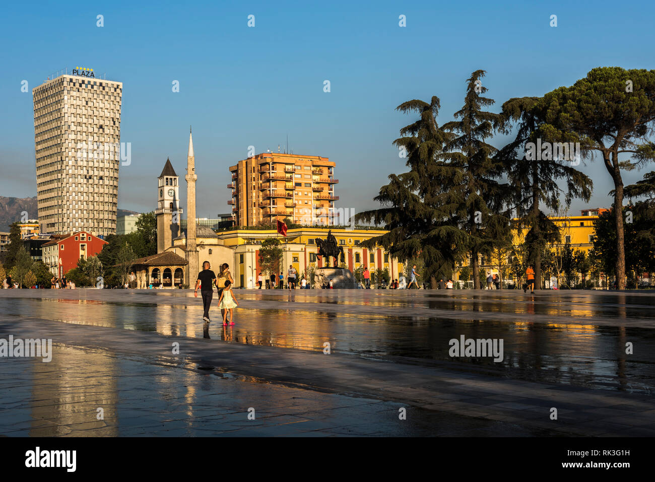 Young family and other locals at Skanderbeg Square in front of the Skanderbeg statue, Et'hem Bey Mosque and a Hotel, Tirana, Albania - Stock Image