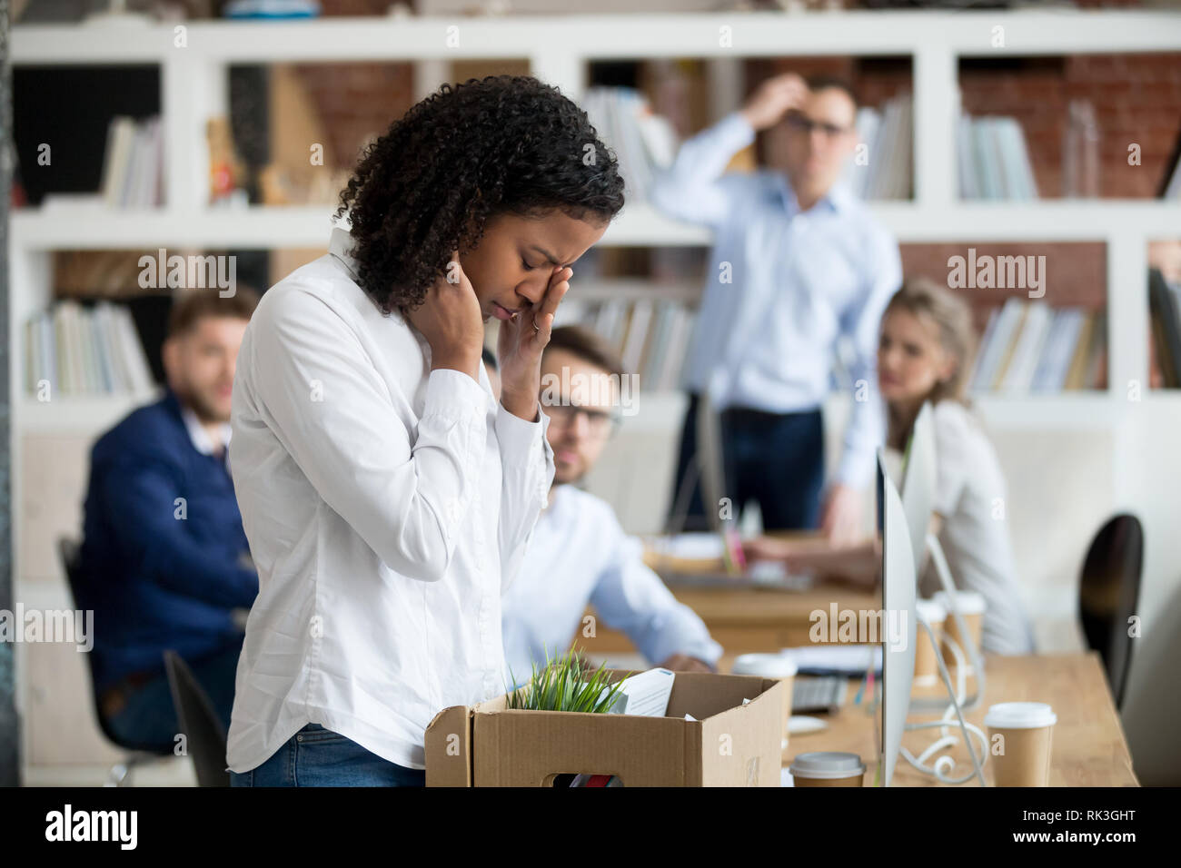 Sad african female employee packing belongings in box got fired - Stock Image