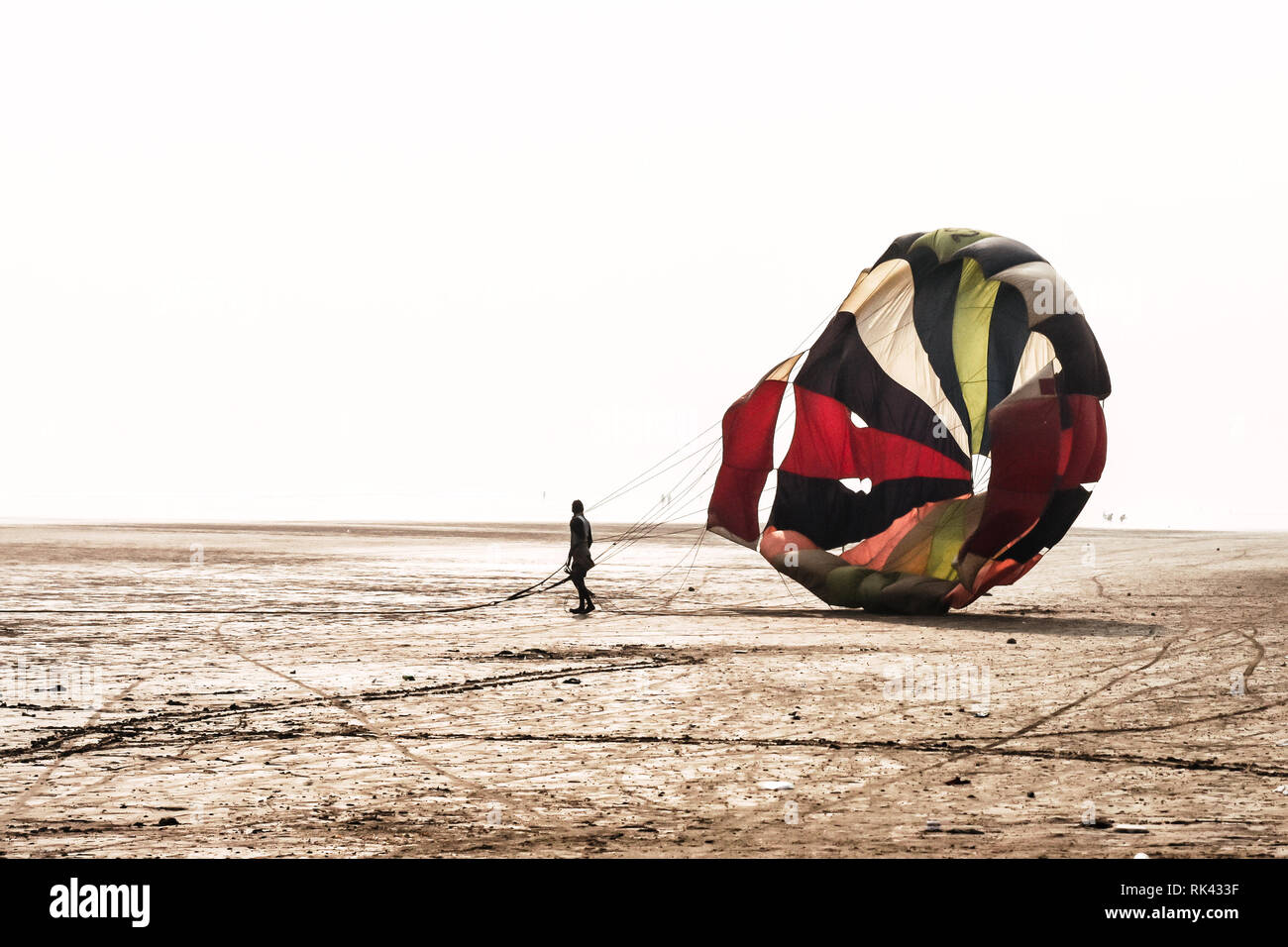 Man do some fold parachute after landing in a famous at Candolim Goa near Baga Beach and Vagator Beach. Yellow and blue wings slings are visible. Stock Photo