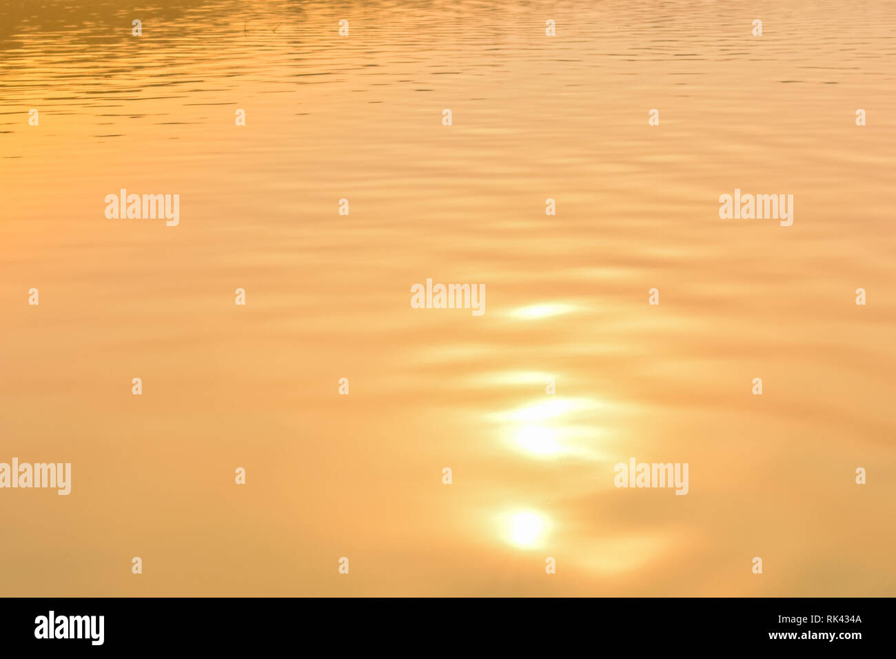 Beautiful sunset water background. The waves on the surface of the river. At twilight times and reflections. Golden and orange colors in the waves. - Stock Image