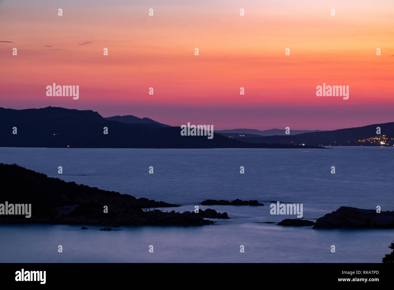 Colourful After Sunset View: Coastline of Northern Sardinia Mediterranean Ocean and the Islands of La Maddalena With Vivid Red Sky and Distant Lights. - Stock Image