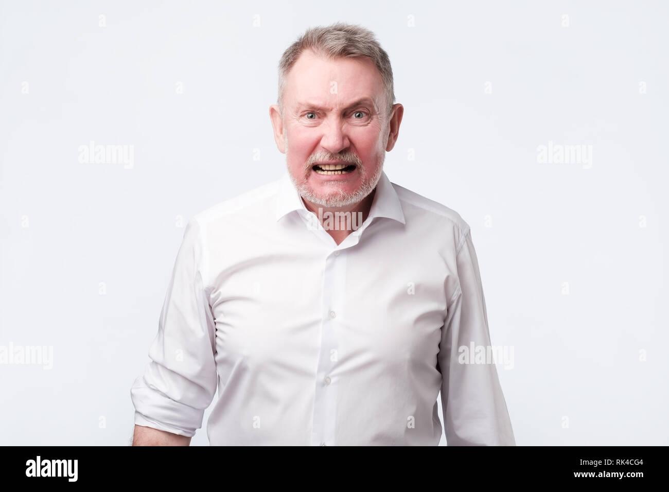 Screaming senior man in white shirt. Negative facial emotion - Stock Image