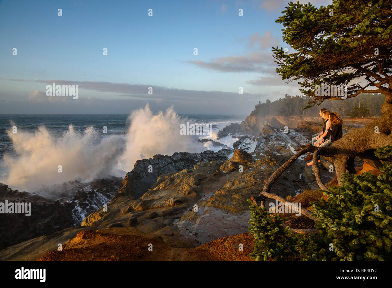 Three women watching storm surf crashing on the rocks at Shore Acres State Park on the southern Oregon coast. - Stock Image