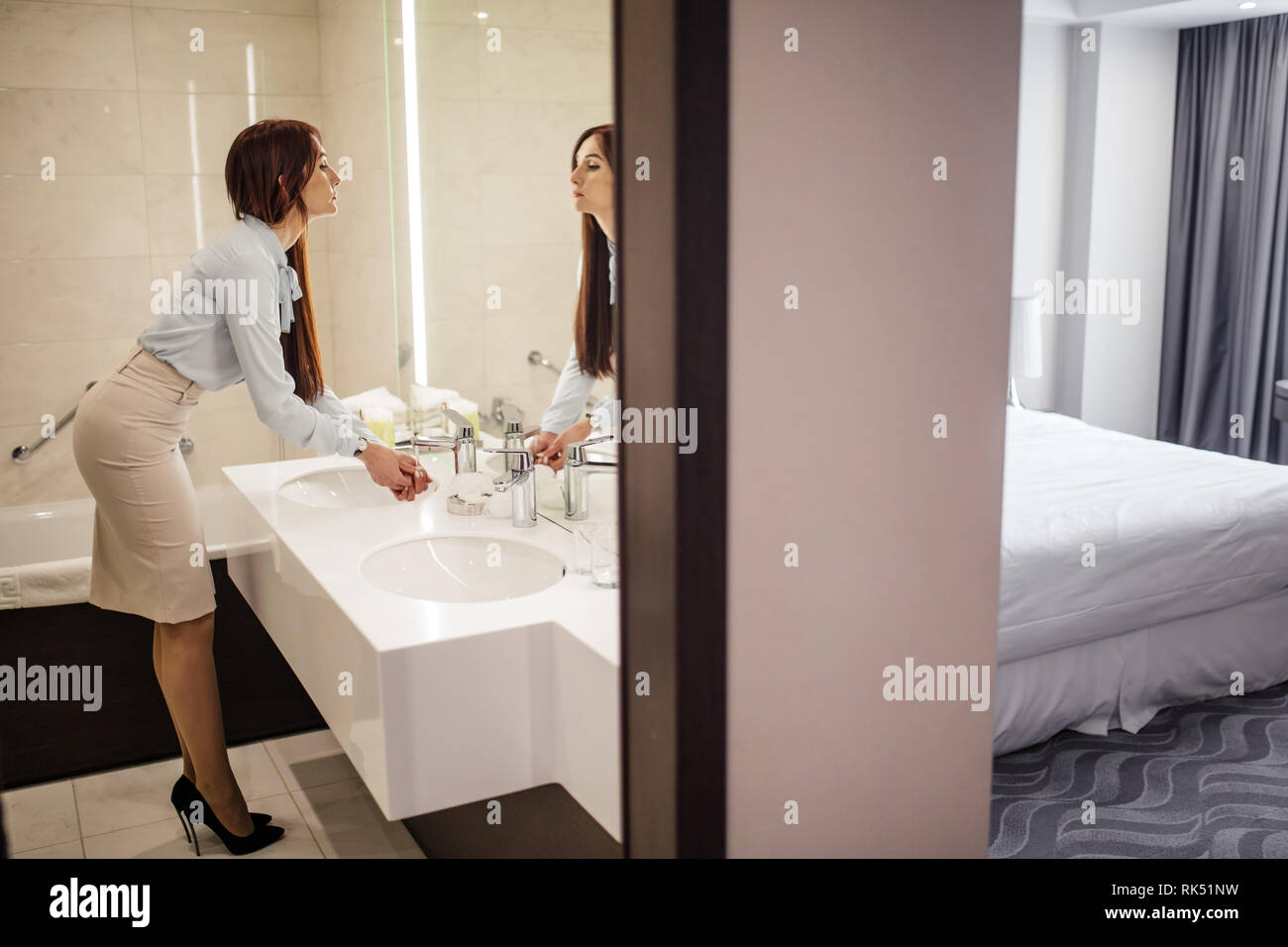 Business lady in dressed in button-down shirt, pencil skirt and stilettos, looking at her reflection in the mirror while washing hands in the bathroom - Stock Image