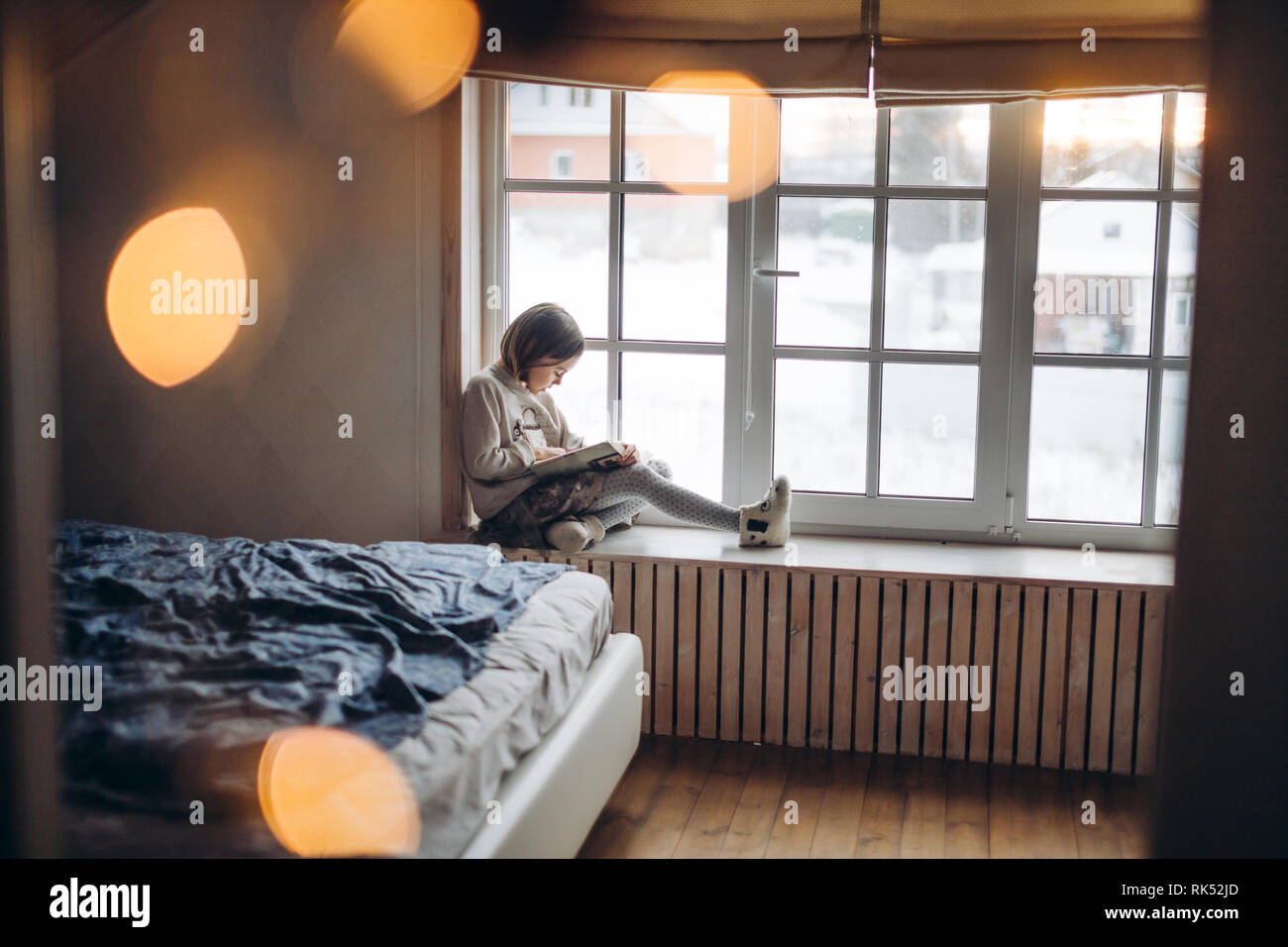 little awesome girl is doing homework on the windowsill in the bedroom. side view full length photo. loneliness. concentration Stock Photo