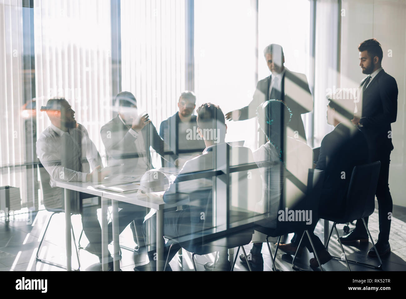 Side view of blurred silhouettes of businessmen talking in conference room, view through the transparent glass wall - Stock Image