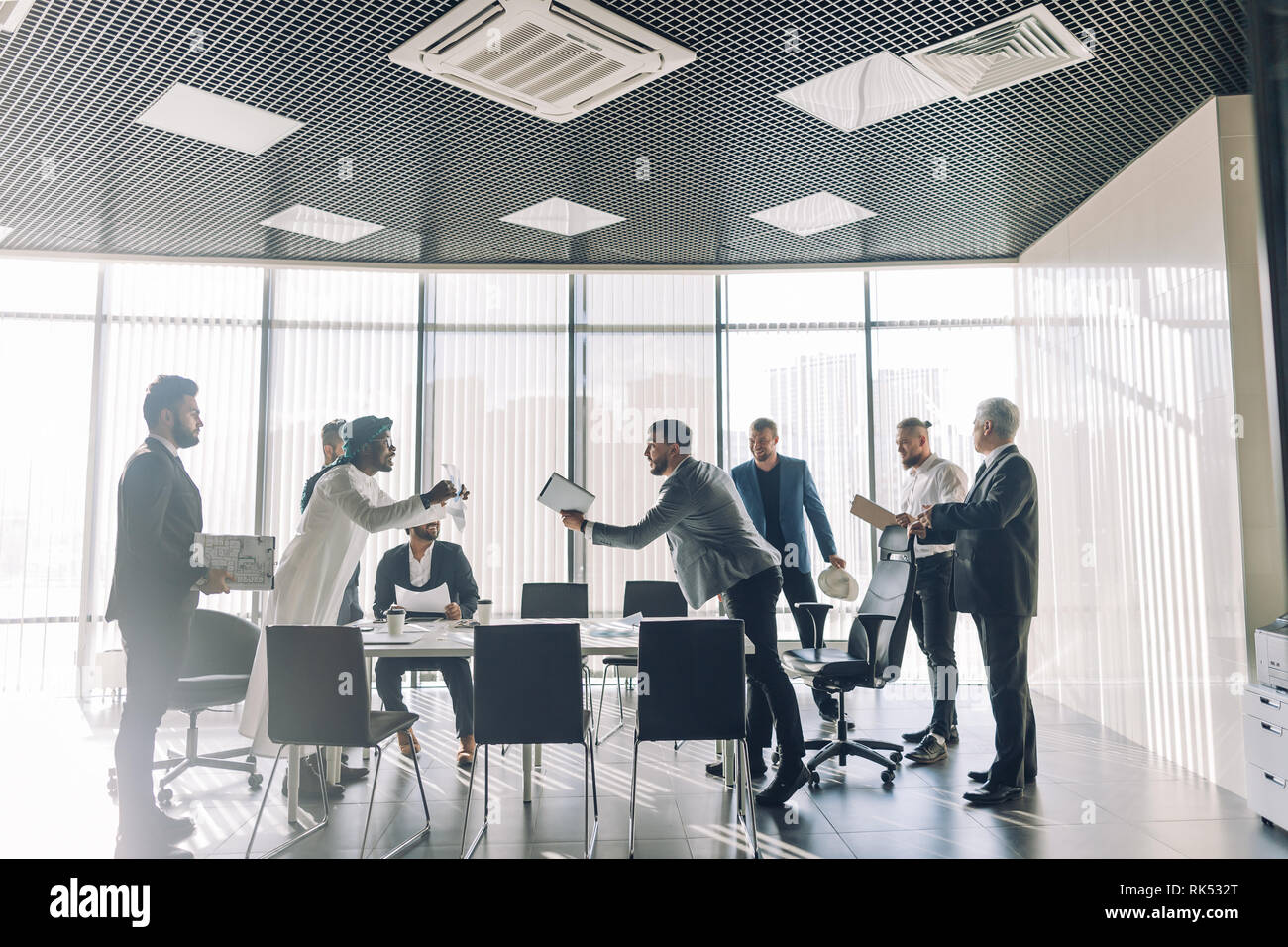Multiethnic business men dressed in formal wear and national arabian clothes debating vivaciously in conference room. Conflicts can be resolved with a - Stock Image