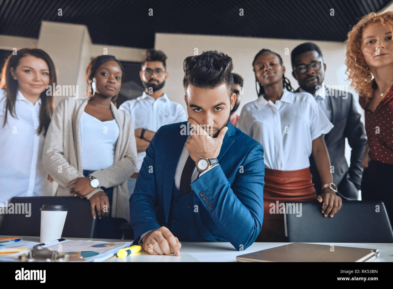 creative smart leader with advanced goals. handsome bearded boss touching his chin while his co-workers standing behind him - Stock Image
