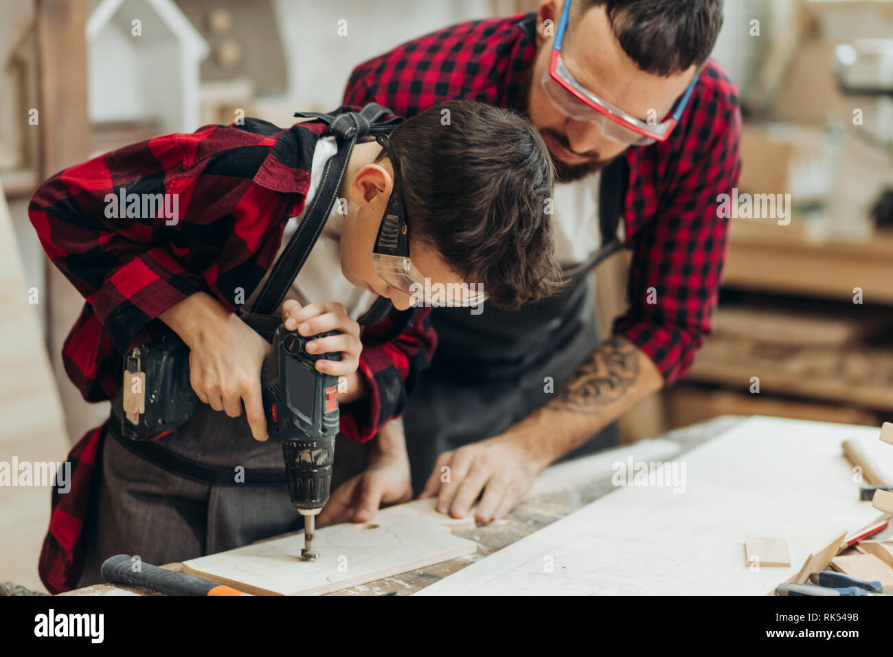 Handsome father and his little pre-teen son dressed in checkered shirts and wearing protective glasses working with drill perforating wood plank at wo - Stock Image
