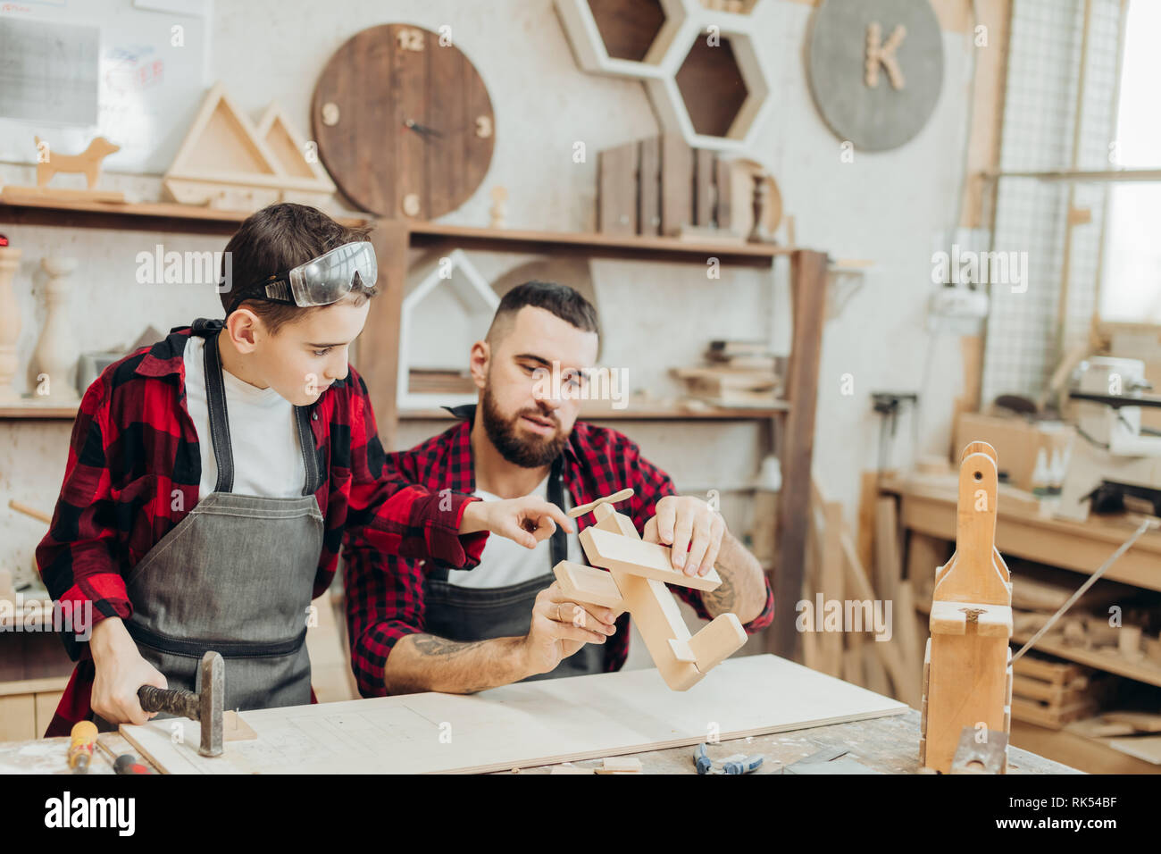 Young caucasian father and his pre-teen son working together in a wooden workshop, building a wooden airplane. Little boy dressed in apron and wearing - Stock Image