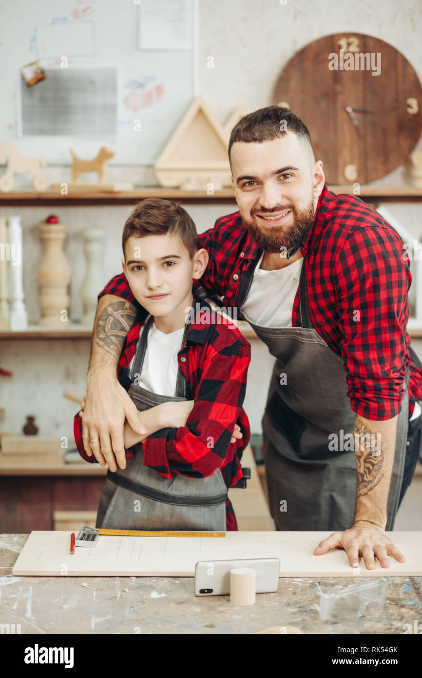 Portrait of father helping his concentrated pre-teen ager son to take measures of wooden plank in workshop during family masterclass of carpentry art. - Stock Image