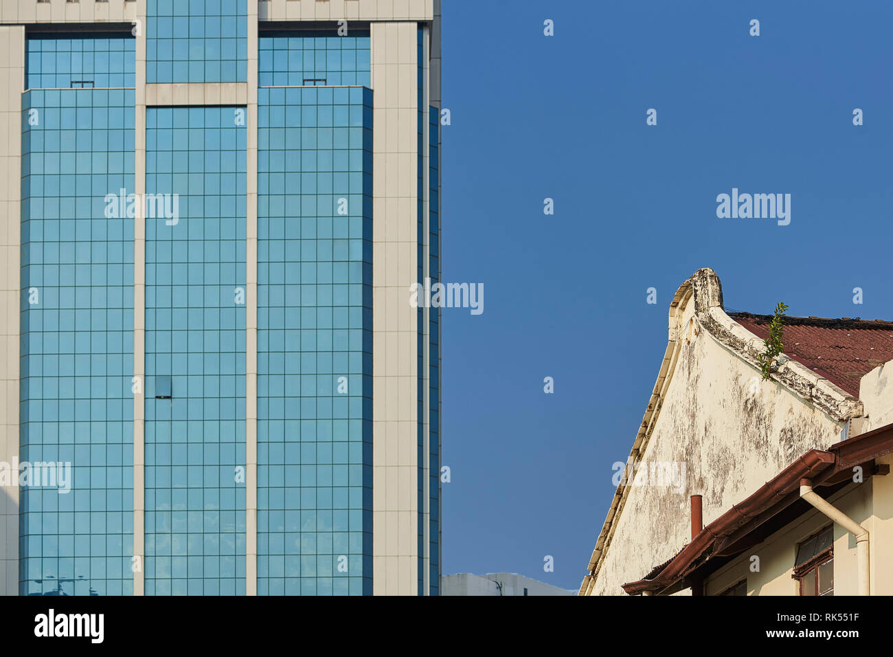 a old shophouse  and a modern building on the street in George Town, Penang, Malaysia - Stock Image