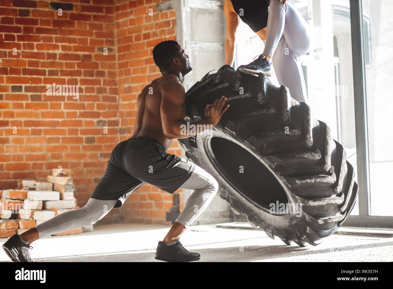 Young muscular african man flipping a tire with a woman on it, working out with weighting Stock Photo