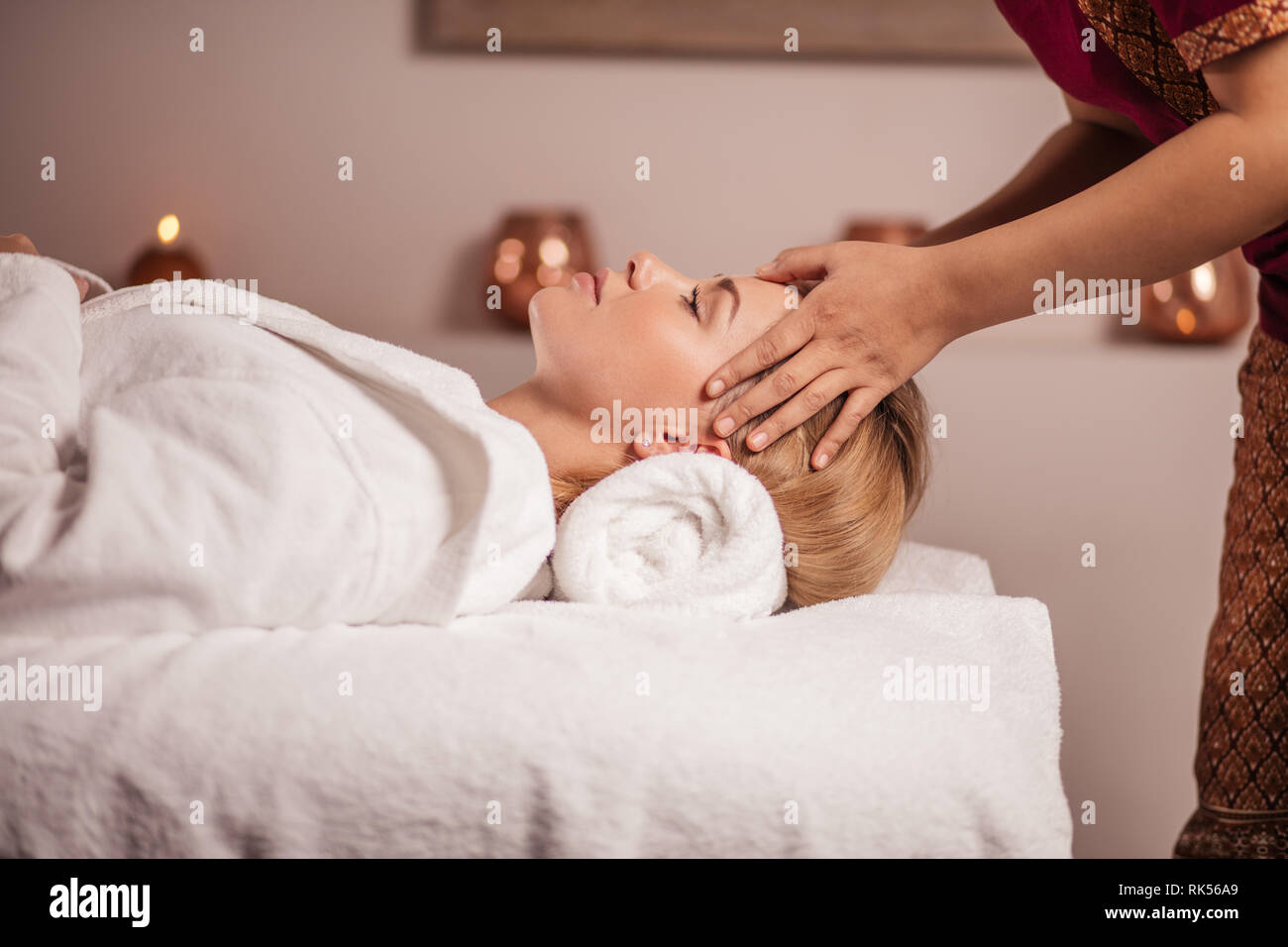 calm beautiful fair-haired woman getting facial massage, medicine treatmnet. reducing stress, weekend, holiday - Stock Image