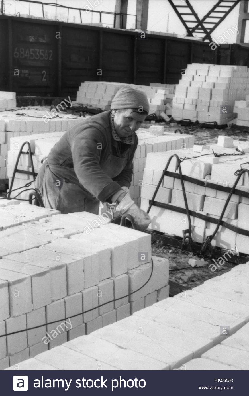 There is no doubt that it is not women's work! However, the woman puts silicate brick on metal pallets, which will be loaded into the wagons later. The brick was manufactured at local factory. Loading of bricks will be made directly from the territory of the railway. The railcars and special tower crane are stand nearby. The woman is wearing overalls. The headscarf is tied on her head. - Stock Image