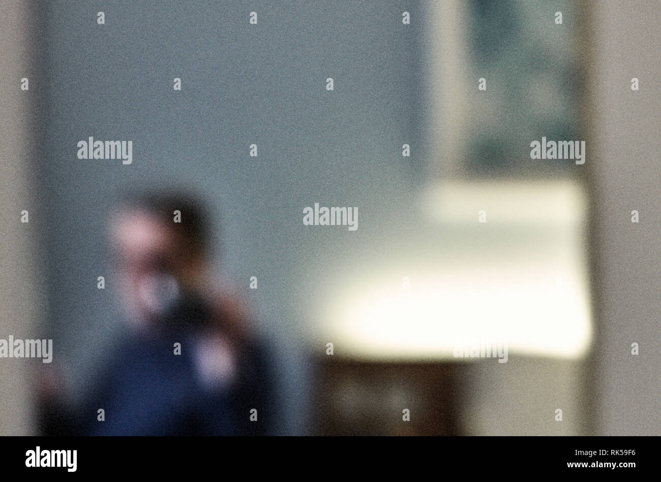 Man in hotel room mirror completely blurred with added grain - Stock Image