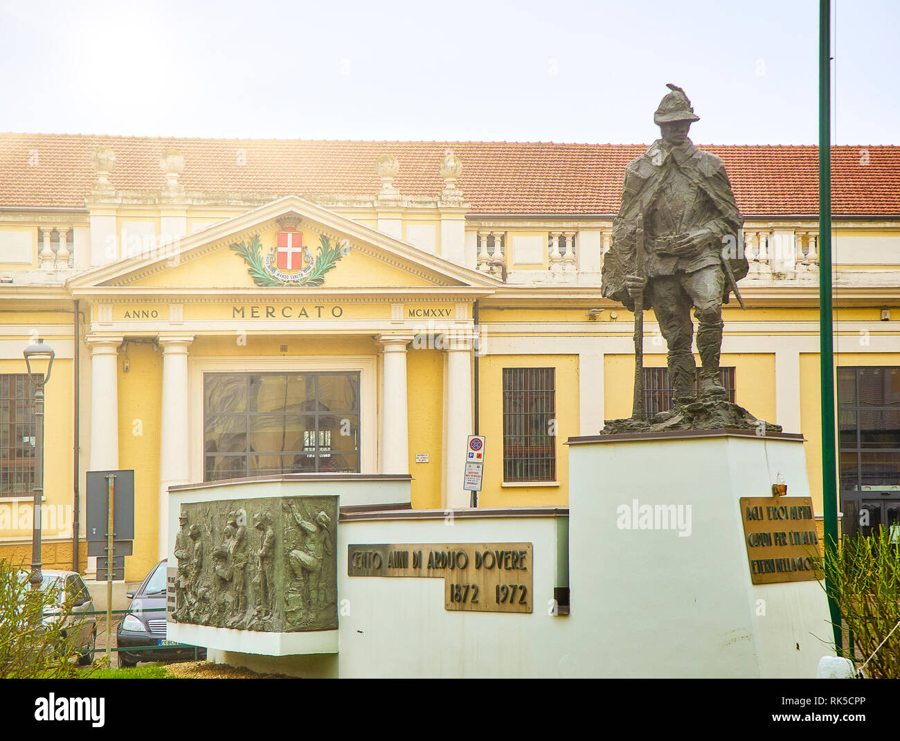 Main facade of The Mercato Coperto market with the Alpino Monument in the foreground. View from the Piazza della Liberta square. Asti, Piedmont, Italy - Stock Image