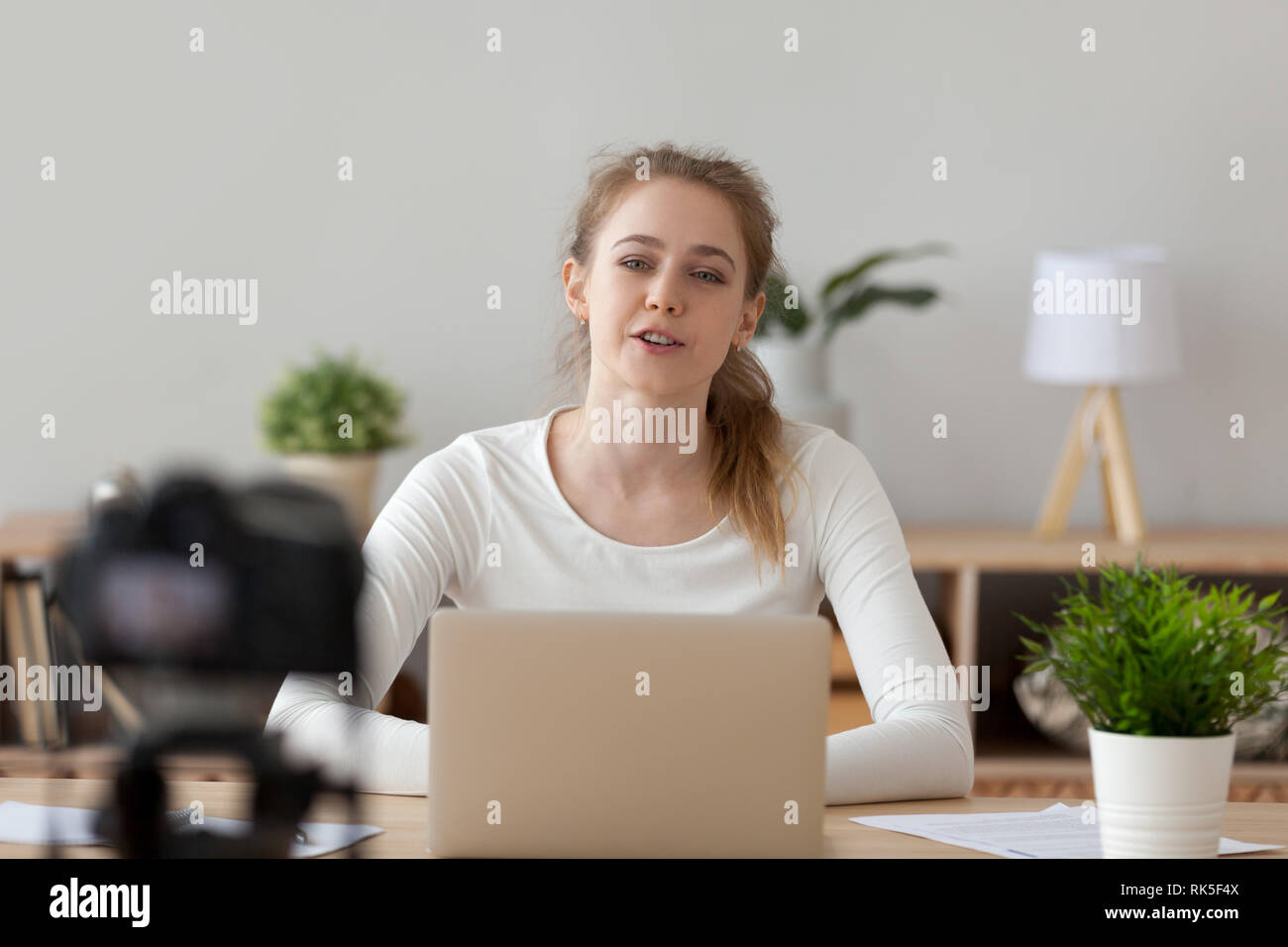 Friendly millennial girl youtuber talking to camera shooting educational video Stock Photo